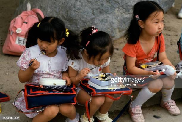 Fillettes sudcoréennes mangeant des kimbap à l'heure du déjeuner en juin 1986 en Corée du Sud