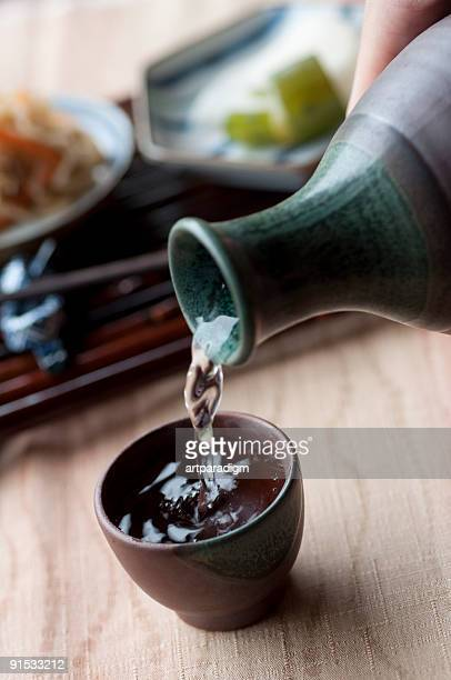 Filling a cup with Japanese sake, and side dishes
