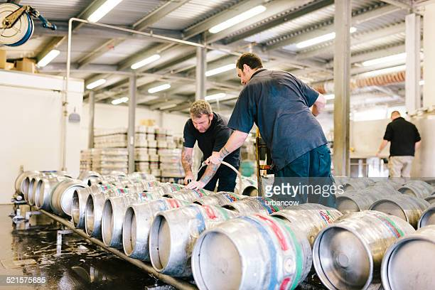 Filling beer kegs with real ale in a brewery warehouse