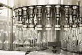Automatic filling machine during operation. Filling glass bottles with liquid.