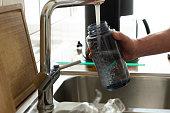 Senior man filling sport water bottle in kitchen.