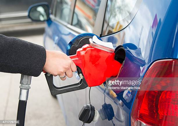 Filling the tank of a car in a gas station Woman fills the tank of her beautiful blue efficient car at a pump in a gas station in Toronto