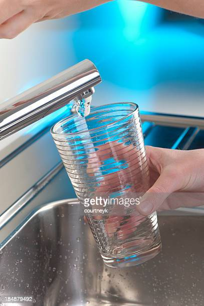 Filling up a glass of water in the kitchen sink