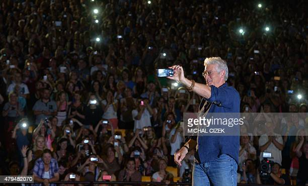 US film actor Richard Gere takes a photo of audience as he presents his film ''Pretty Woman'' at the 50th Karlovy Vary International Film Festival in...