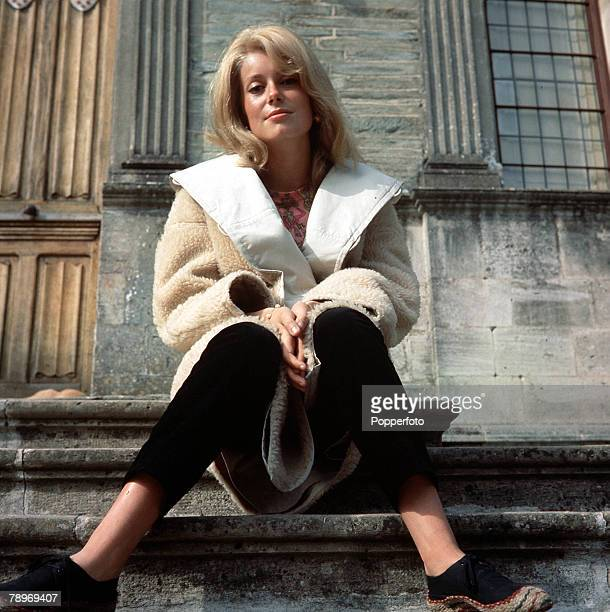 Film Actress Catherine Deneuve poses for the camera sitting down on some steps 1963