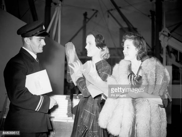 Film actresses Honor Blackman centre and Lana Morris run their fingers through the new nylon stockings watched by a ship's officer aboard the luxury...
