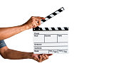 Hand holding a film clapboard slate or movie slate isolated on white background, with clipping path.
