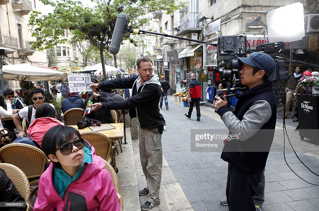 A film crew from Chuan Films shoots footage of Chinese actors on the set of 'The Old Cinderella' at the Ben Yehuda pedestrian mall in Jerusalem, Israel, on Friday, April 19, 2013. The Bank of Israel governor said Europe remains the weak link in the world economy and European Union officials need to tackle the continent's banking difficulties. Photographer: Ariel Jerozolimski/Bloomberg via Getty Images