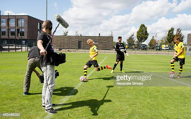 A film crew video Marcel Schmelzer and DongWon Ji in action during the Borussia Dortmund team presentation on August 11 2014 in Dortmund Germany