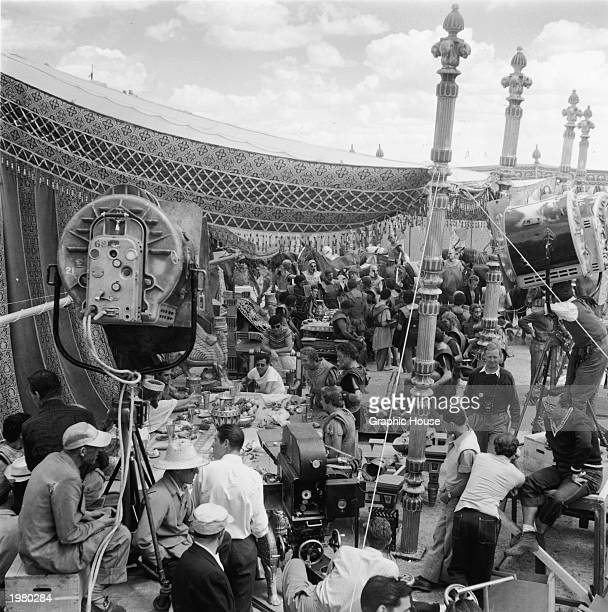 Film crews prepare to a shoot an outdoor banquet scene as actors wearing Roman costumes sit at tables under period tapestries during the production...
