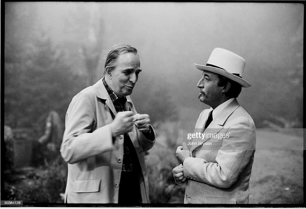 Film director Ingmar Bergman (L) talking with actor Peter Sellers while he visits a movie set during a trip to Hollywood.