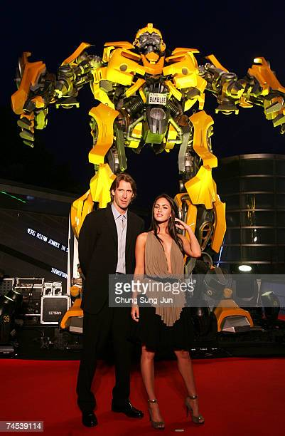 S film director Michael Bay and actress Megan Fox attend in front of Bumble Bee before a press conference to promote their new film 'Transformers' on...