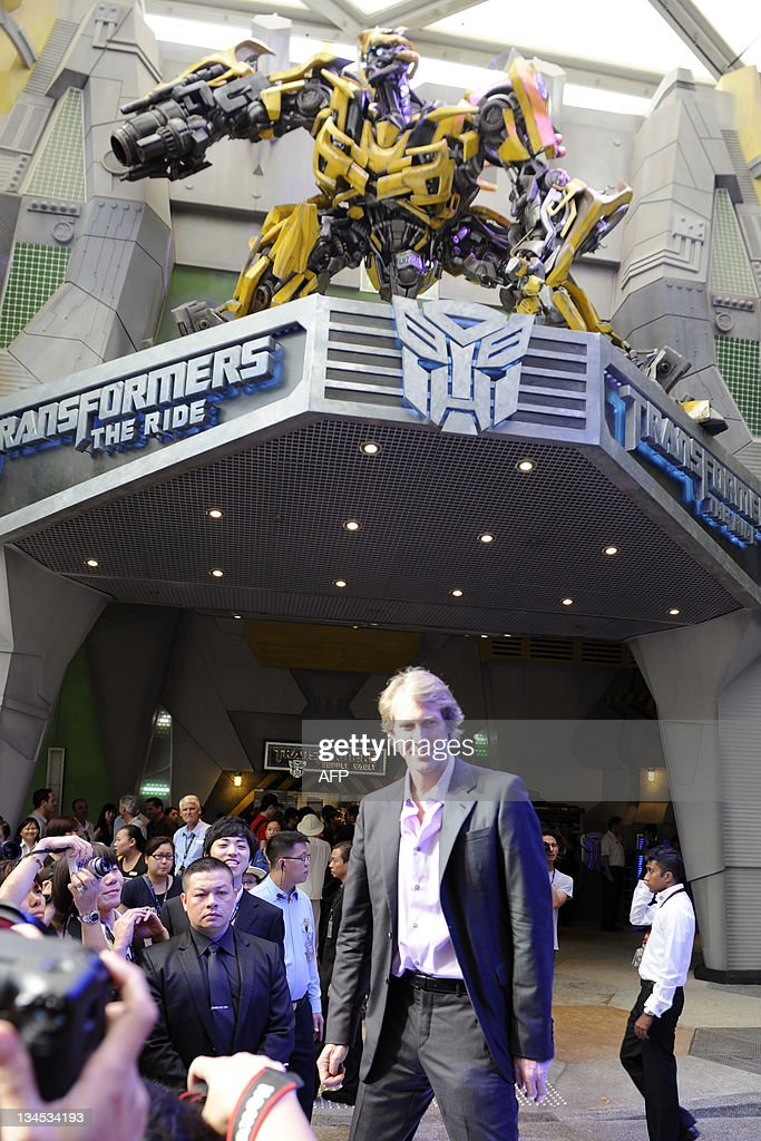 US film director Michael Bay poses in front of an Autobot model during the media preview for 'Transformers: The Ride' at Universal Studios Singapore on December 2, 2011. The themed amusement park ride, due to open for the public on December 3, is based on the Transformers movie franchise directed by Bay.