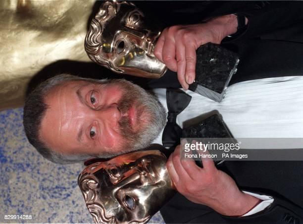 Film Director Mike Leigh holds his two BAFTA awards for Secrets Lies at the Royal Albert Hall in London during the award ceremony
