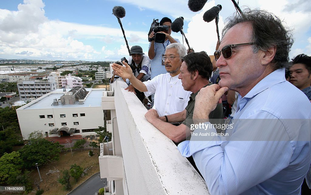 Film Director Oliver Stone looks at the U.S. Marine Corps Air Station Futenma from the rooftop of Okinawa International University on August 13, 2013 in Ginowan, Okinawa, Japan.