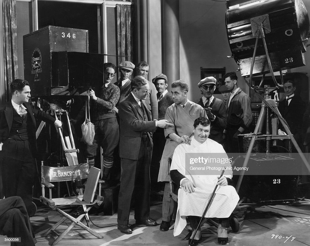 Film director Rowland Lee directing Tony the barber to cut the hair of George Bancroft on the set of the film 'Ladies Love Brutes'