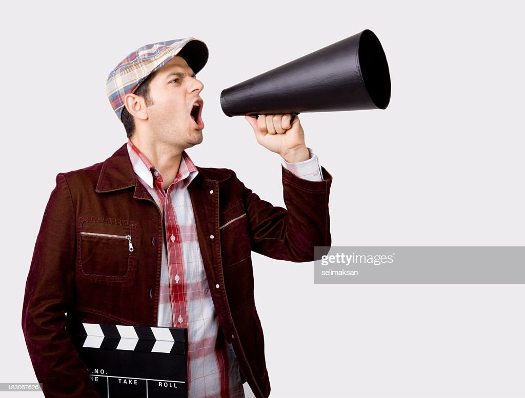 Film Director Shouting On Megaphone While Holding Film Slate