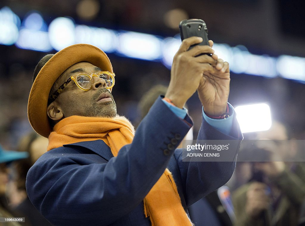 US film director Spike Lee takes pictures with his mobile phone of the New York Knicks players ahead of the NBA basketball game against The Detroit Pistons at the O2 Arena in London on January 17, 2013. AFP PHOTO / ADRIAN DENNIS