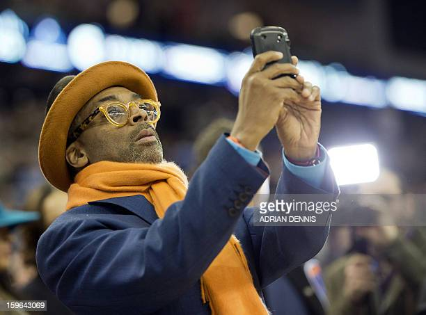US film director Spike Lee takes pictures with his mobile phone of the New York Knicks players ahead of the NBA basketball game against The Detroit...