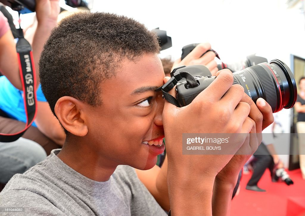 US film director Spike Lee's son, Jackson, takes pictures of his father during the photocall of 'Bad 25' during the 69th Venice Film Festival on August 31, 2012 at Venice Lido. 'Bad 25' is presented out of competition. AFP PHOTO / GABRIEL BOUYS
