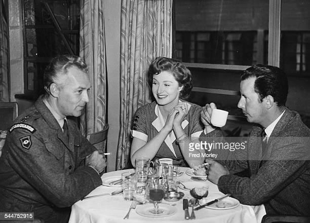 Film director Terence Young talking to actors Ralph Clanton and Helen Cherry around a table on the set of the film 'They Were Not Divided' at Denham...