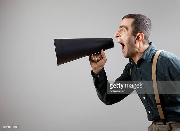 Réalisateur portant chemise et bretelles crier sur Porte-voix