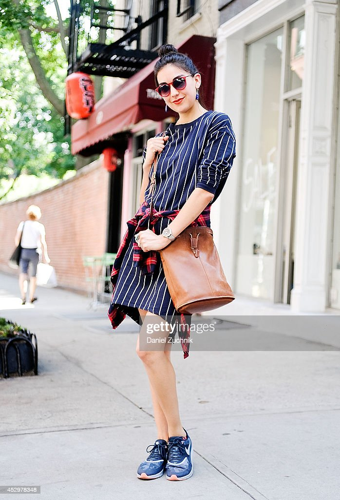 Film Editor Jenny Salinas is seen around Nolita wearing an H&M dress, Zara flannel, Nike sneakers, vintage sunglasses, handmade earrings and a vintage Coach bag on July 31, 2014 in New York City.