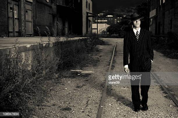 film noir style gangster walking in an alley