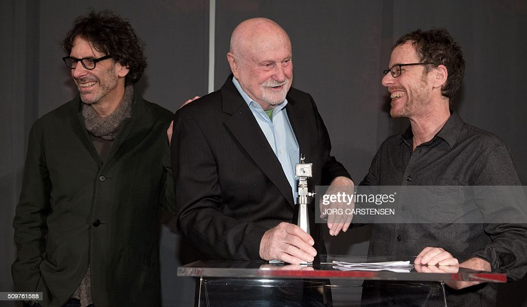US film producer Ben Barenholtz (c) poses with the Berlinale Camera award, flanked by US film directors Joel Cohen (L) and Ethan Coen (R) on February 12, 2016 in Berlin as tribute for his collaboration with Berlin Film Festival. / AFP / dpa / Jörg Carstensen / Germany OUT