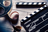A clapperboard and film reel are positioned on a wooden table.  The film reel is a light metal and is partially unspooled.  Next to it is a black-and-white film slate with the clapper opened.  There i