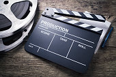 Movie clapper, film reel and notepad on a wooden background