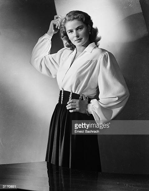 Film star Ingrid Bergman wearing a blouse with full sleeves gathered to tight cuffs a broad belt and soflty draped skirt