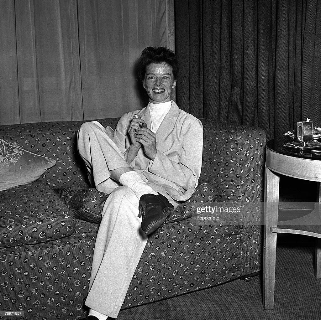 Film star Katherine Hepburn smiling as she sits on a comfortable sofa at a press reception at Claridges, London, 1951