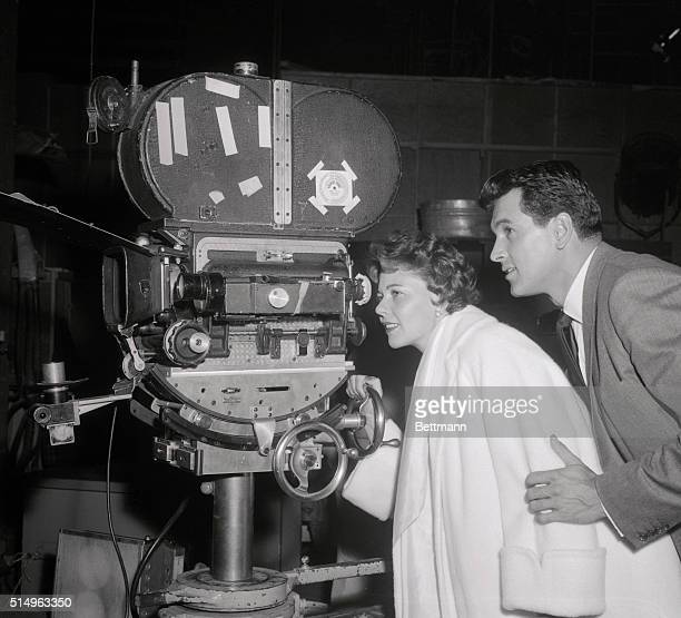 Film star Rock Hudson explains the movie camera to his new bride the former Phyllis Gates on the set of his new movie Written on the Wind They're in...
