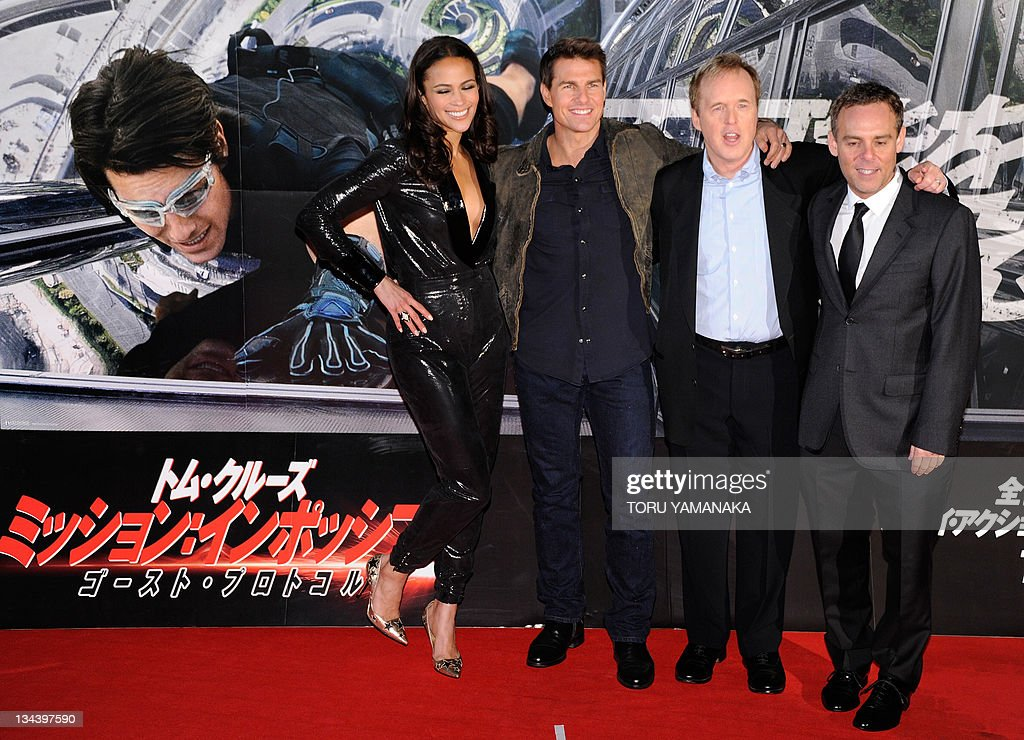 """US film star Tom Cruise (2nd L), actress Paula Patton (L), director Brad Bird (2nd R) and producer Bryan Burk (R) pose for photographers during a fan meeting to promote their latest movie """"Mission Impossible - Ghost Protocol"""" in Tokyo on December 1, 2011. AFP PHOTO/Toru YAMANAKA"""