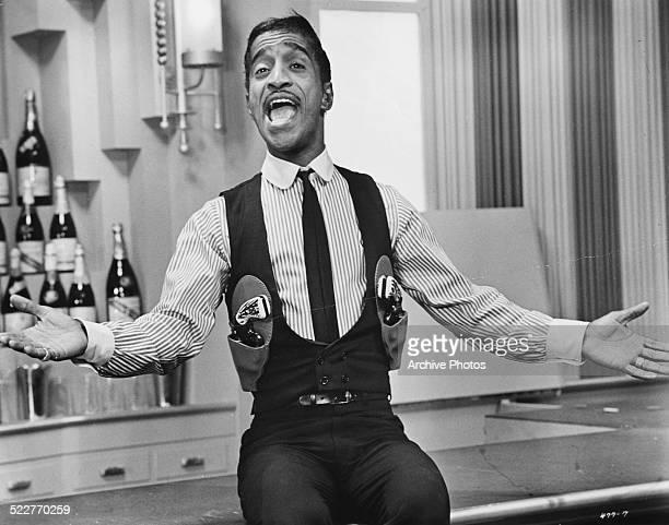 Film still of actor and singer Sammy Davis Jr wearing a suit and two holstered pistols circa 1955