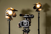 Filming in a Studio or interior. Video camera (camcorder) and two halogen spotlights directional lights with Fresnel lenses.