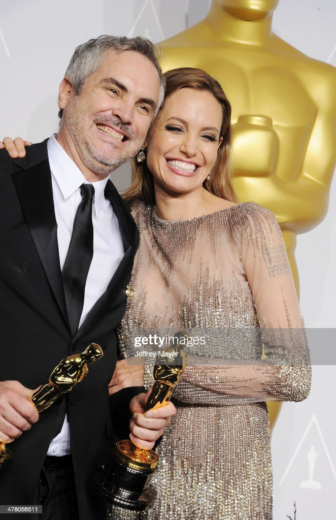 Filmmaker <a gi-track='captionPersonalityLinkClicked' href=/galleries/search?phrase=Alfonso+Cuaron&family=editorial&specificpeople=213792 ng-click='$event.stopPropagation()'>Alfonso Cuaron</a>, winner of Best Achievement in Directing for 'Gravity' (L) and actress <a gi-track='captionPersonalityLinkClicked' href=/galleries/search?phrase=Angelina+Jolie&family=editorial&specificpeople=201591 ng-click='$event.stopPropagation()'>Angelina Jolie</a> pose in the press room during the 86th Annual Academy Awards at Loews Hollywood Hotel on March 2, 2014 in Hollywood, California.