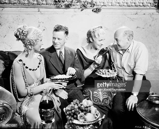 Filmmaker Cecil B DeMille eating food with a group of people during the making of the film 'Samson and Delilah' for Paramount Pictures 1949