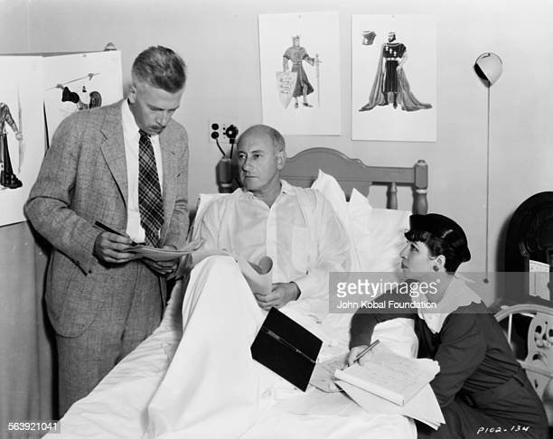 Filmmaker Cecil B DeMille recuperating in bed as his staff discuss the making of the film 'Samson and Delilah' with him for Paramount Pictures 1949
