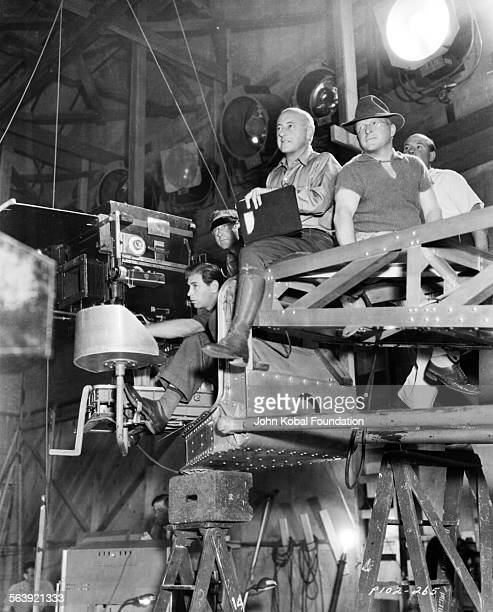 Filmmaker Cecil B DeMille sitting on a camera rig with members of his crew on the set of the film 'Samson and Delilah' for Paramount Pictures 1949