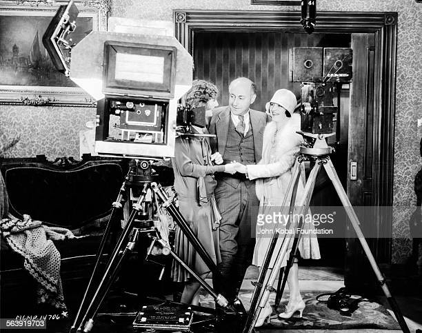 Filmmaker Cecil B DeMille talking to two actresses on the set of the film 'The Godless Girl' for MGM Studios March 30th 1929