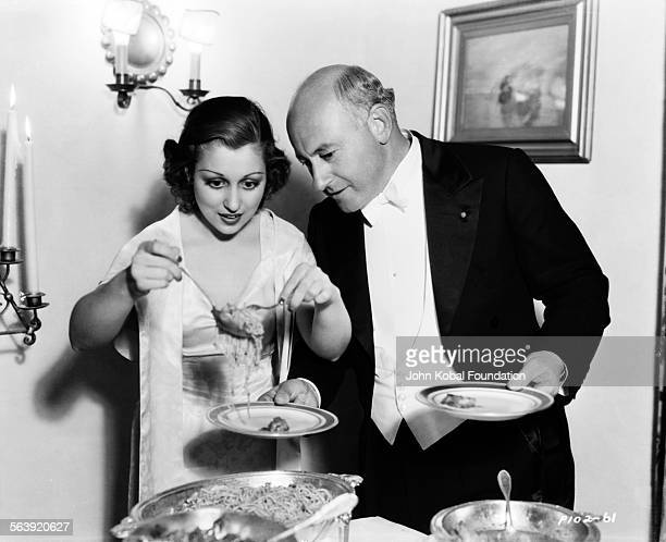 Filmmaker Cecil B DeMille wearing a tuxedo as he helps to serve food at a party for Paramount Pictures 1949