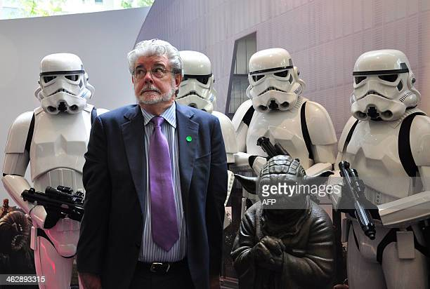 Filmmaking legend George Lucas of Disney's Lucasfilms poses with Stormtroopers and Yoda characters from Lucas' Star Wars films at the opening of...