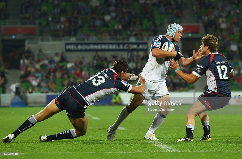 Filo Paulo of the Blues is challenged by Mitch Inman and James O'Connor of the Rebels during the round seven Super Rugby match between the Melbourne Rebels and the Auckland Blues at AAMI Park on April 5, 2012 in Melbourne, Australia.