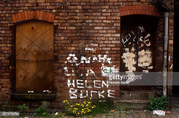 A filthy alleyway in Toxteth Liverpool amid sociallydeprived streets and terraced housing Graffiti of girls' names has been painted on to the brick...