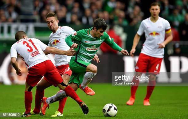Fin Bartels of Bremen is challenged by Diego Demme of Leipzig and Stefan Ilsanker of Leipzig during the Bundesliga match between Werder Bremen and RB...