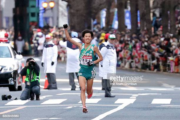 Final runner of Aoyama Gakuin University Yuya Ando raises his arm as he celebrates winning during day two of the 93rd Hakone Ekiden on January 3 2017...