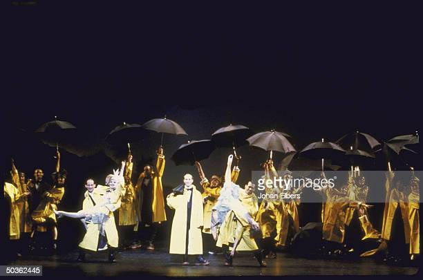 Final scene in the play Singin' in the Rain with cast in raincoats and umbrellas dancing in downpour