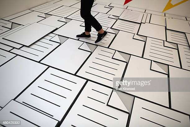 Final year art student Paul Schneider walks through his work entitled 'Office Party' on June 11 2014 in London England The piece makes up part of the...